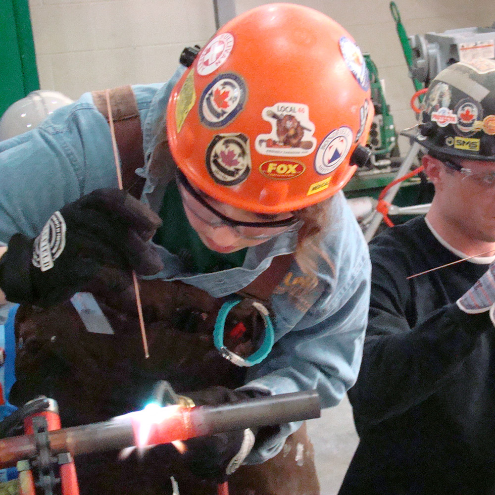 workers working on welding a pipe